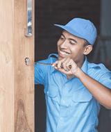 Smiling Locksmith working on wooden door